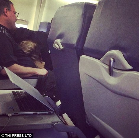 This couple find a bizarre position to adopt on their flight