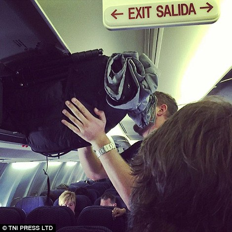 A man struggles to squeeze all his luggage in the overhead bin