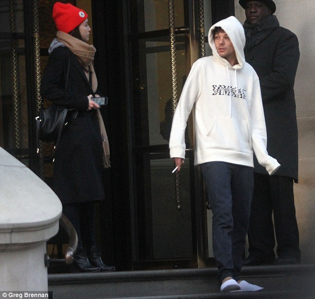 Baring up: Just 48 hours after he paid tribute to his late mother on the X Factor Louis Tomlinson put on a brave face as he emerged from his hotel in London on Monday morning