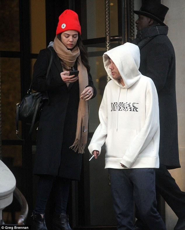 Support network: Accompanied by his girlfriend Danielle Campbell, the 24-year-old One Direction star looked slightly dishevelled as he emerged into the cold winter air for a cigarette