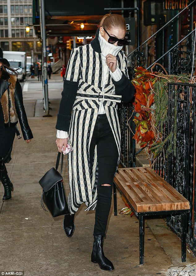 Earning her fashion stripes! Gigi, meanwhile, was practically bundled up from head-to-toe in a white knit turtleneck, belted coat, ripped jeans, and ankle boots
