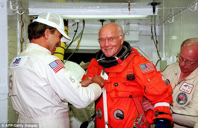 Glenn gets a hand from  technicians moments before boarding the US space shuttle Discovery on October 9, 1998 (above)
