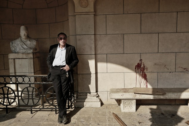 A man stands near bloodstains on a wall at the scene inside the St. Mark Cathedral in central Cairo, following the bombing