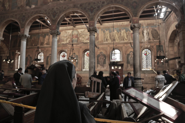 An Egyptian Coptic nun weeps as she looks at damages inside St Mark's Cathedral in central Cairo, following the bombing