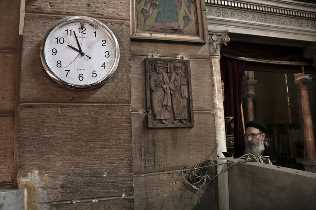 A Coptic clergyman gazes at the wrecked chapel as a damaged clock shows the time when the bomb was thrown in central Cairo