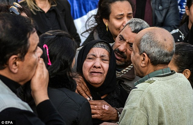 Relatives of the victims of yesterday's suicide bombing mourn during the burial service. The attacker was a 22-year-old Muslim fundamentalist