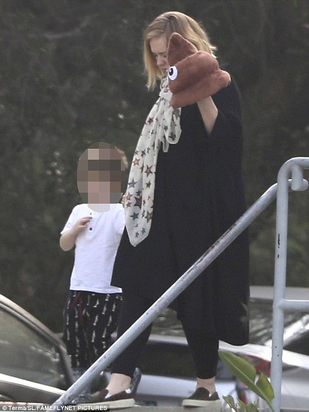 Don't mind me: Sporting a trademark black smock dress over a pair of matching leggings, Adele had her hands full as she held onto her only child with partner Simon Konecki while juggling the boy's distinctive 'poop emoji' hat