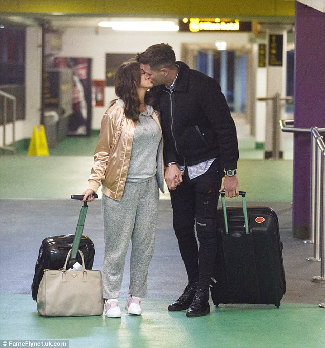 Pucker up: Vicky Pattison stole a cheeky kiss from her boyfriend John Noble as they arrived back at Gatwick airport on Sunday after a weekend break in Vienna