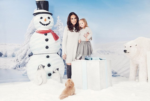 Glam mum: Wearing a jumper dress and thigh-high boots, the F1 heiress, 32, beamed as she wrapped her arms around the cute toddler while posing against a snowy backdrop
