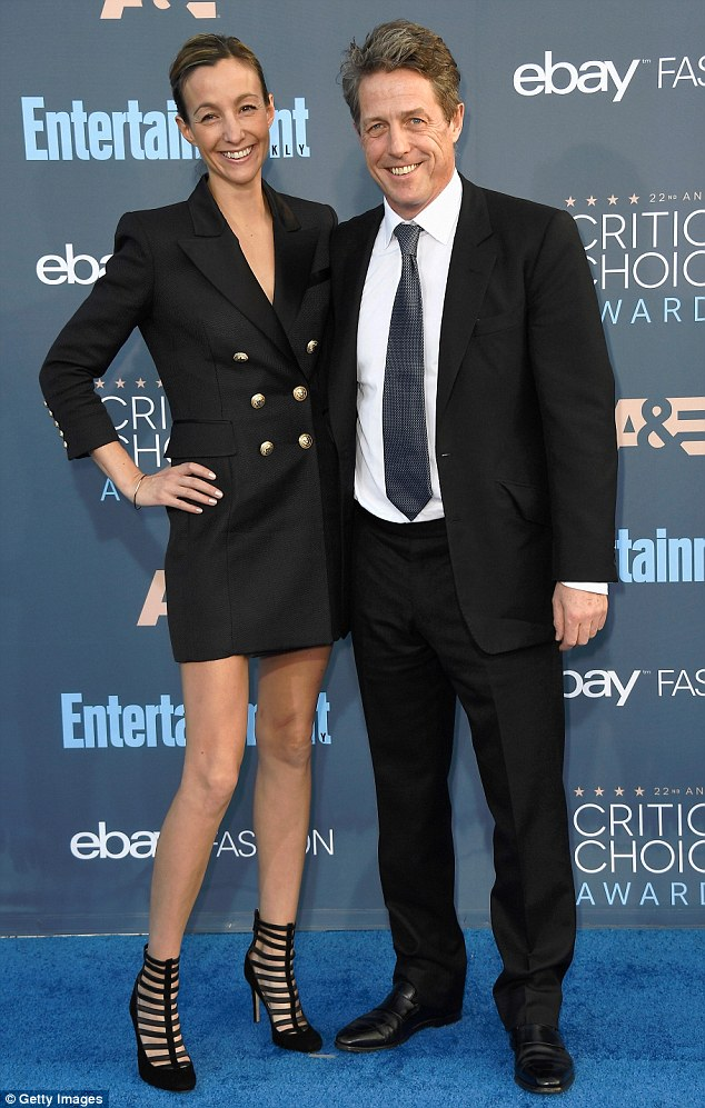 Clean-cut couple:The actor looked his usual dapper self in a simple but classic suit and tie combination - while his partner flashed her legs in a chic black dress, styled like a blazer
