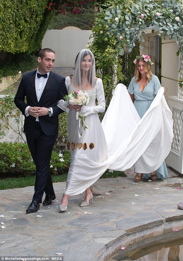 Big day: Janice Dickinson looked ecstatic to be putting her best foot forward as she was seen - in world exclusive photos - going up the aisle for the fourth time on Saturday accompanied by her son Nathan and daughter Savannah