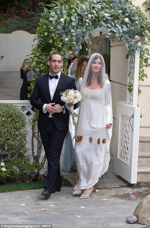Virginal: The mother of two - who has son Nathan with second husband Simon Fields and shares daughter Savannah with former boyfriend Michael Birnbaum - covered her face with a white veil as she made her way to her fiance of four years