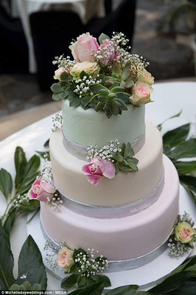 Sweet treat: Their wedding cake was a stunning three-tiered red velvet cake, which was iced in pastel pink, yellow and green and decorated with roses