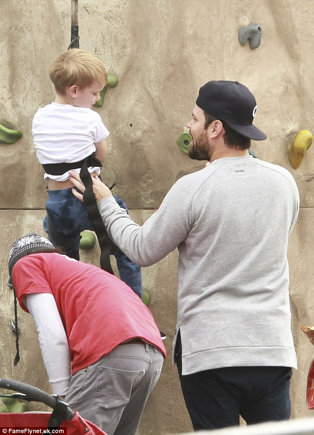 Father knows best: Comrie gives his son Luca a bit of a boost as the boy makes his way up the climbing wall at the venue during the Saturday trip