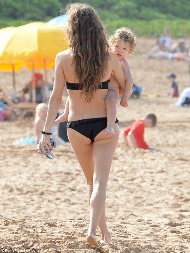 Bun in the sun: She showcased her athletic derriere as she went for a walk in the sand