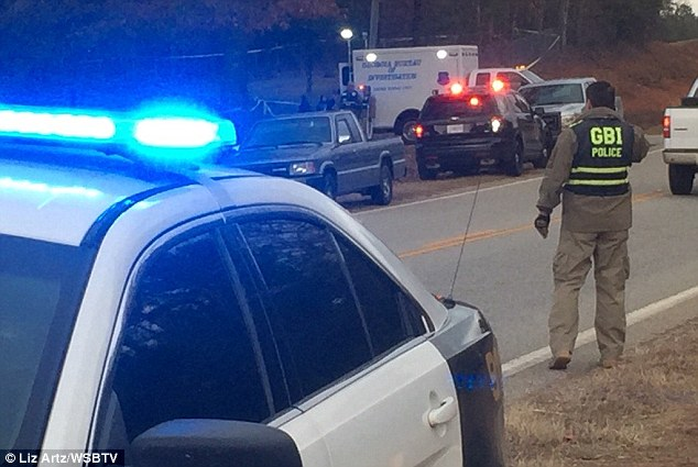 Tragedy: Two Georgia police officers were shot while serving a warrant at around 2.10am on Monday morning (police on the scene above)