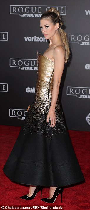 Stunning: Shewas positively beaming in her shimmering gold and black strapless number as she floated down the red carpet