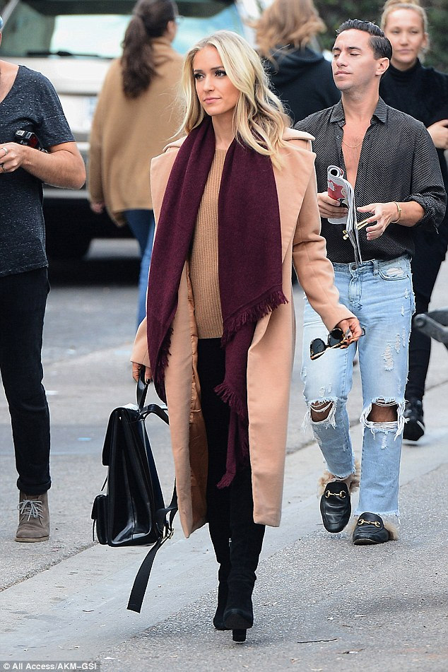 Stylish: The 29-year-old reality television star layered an elegant nude long coat over a matching sweater