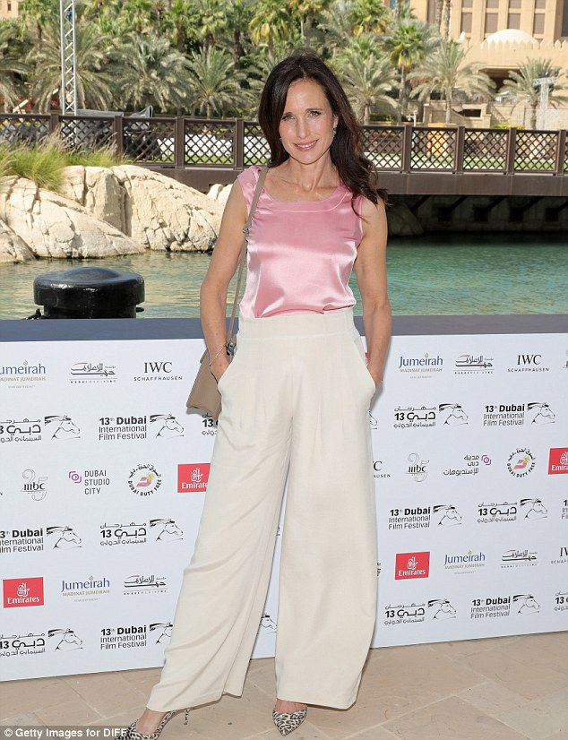 Immaculate:The Four Weddings And A Funeral star showed off her trim waist in a baby pink silk top and elegant cream wide-legged trousers