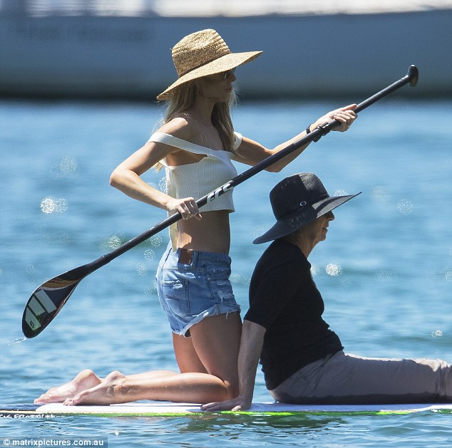 Stylish on the water: While kneeling tall on the board, the 32-year-old model showed off her toned torso as she dressed in a crop-top and denim mini-shorts