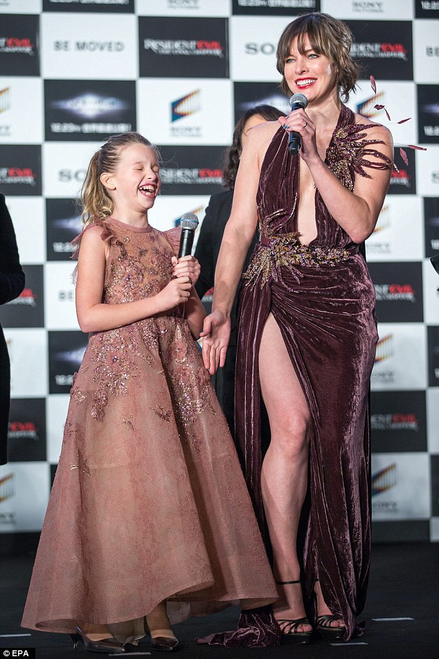 Sky-high shoes: Teaming the dress with a pair of sky scraper black stilettos, the A-List beauty defined her gym-honed pins further and certainly made her daughter laugh as she took to the mic