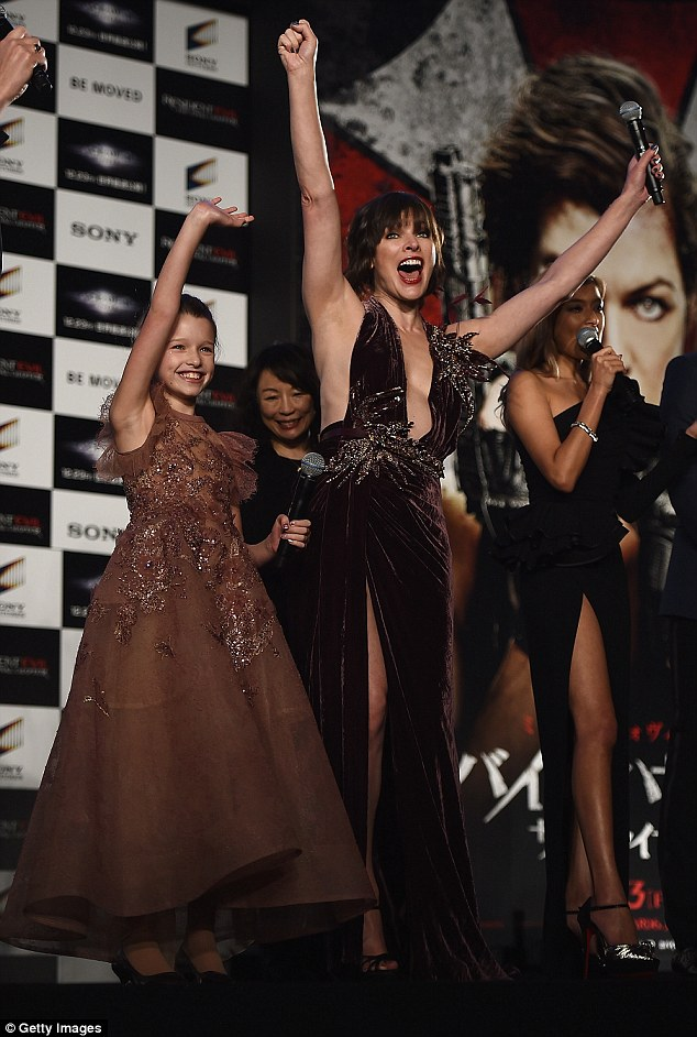 Sartorial sass: Thanks to the cut of the halter-neck neckline, Milla flashed more than a hint of her cleavage, while a thigh-high slash  allowed the former model to showcase her lithe legs as she and Ever waved to the crowd