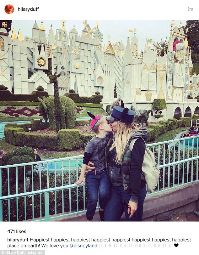 So cute:In the photo the blonde actress kisses her son sweetly on the lips while posing in front of It's a Small World