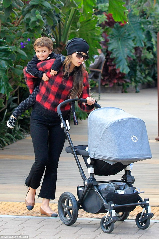 Mom of two: The Legal Weapon and Fast & Furious star wore a red and black fluffy check jacket and a large beanie for the outing with her kids