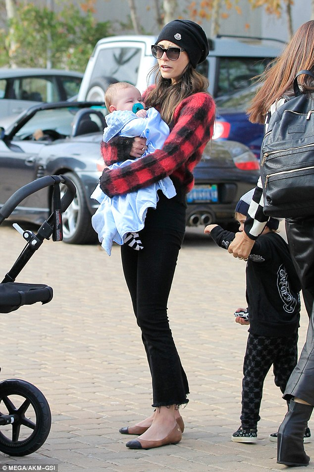 Baby Ryan, who was born to a surrogate in June, wore stripy socks and was wrapped in a blue blanket as his mom picked him up out of the stroller for a cuddle
