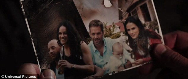 Fond memories: Dominic Toretto looked at an old picture featuring his pal Brian O'Conner, played by the late Paul Walker