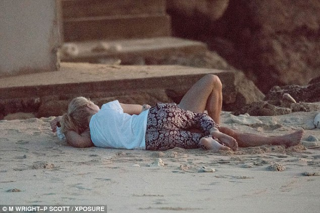 Tempestuous troika: Lottie cosied up to Alex on the cool Barbadian sand as the sun set on the horizon