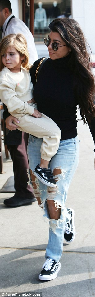 Hot mama! Kardashian rocked ripped jeans, sneakers, and a black turtleneck
