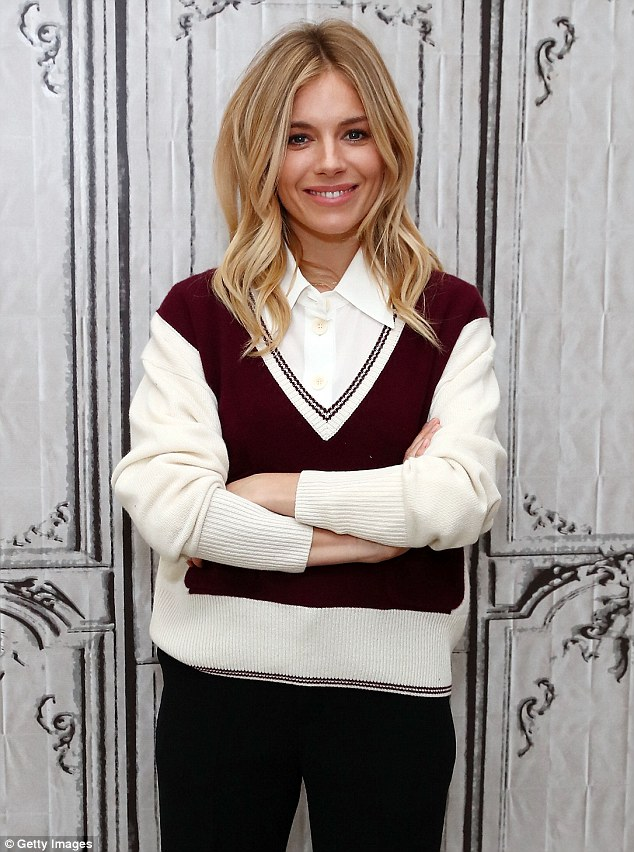 Chic and cheerful: Concealing her enviable figure, the Burnt star layered a maroon cricket style jumper over a white shirt which she teamed with cropped black trousers