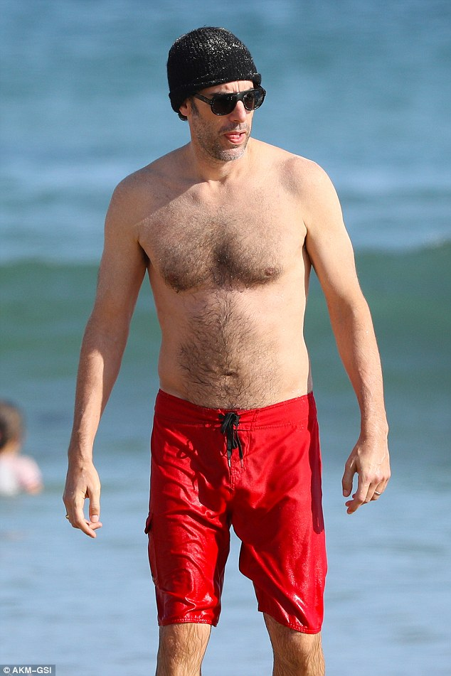 Stylish: Sacha meanwhile showed off his incredibly youthful physique as he strutted along the beach in his red board shorts paired with a black hat