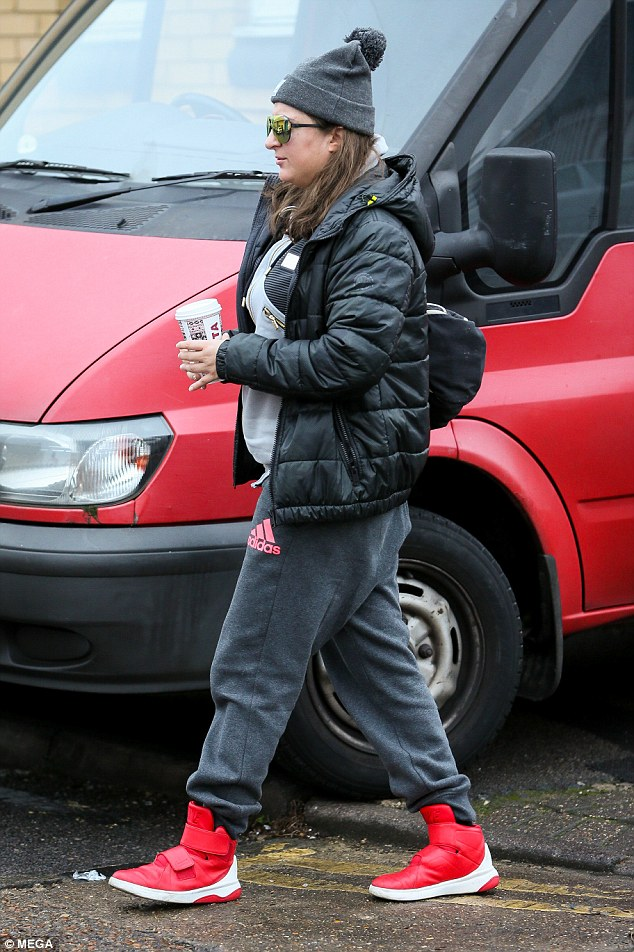 Always looking fresh: The 35-year-old eccentric rapper sported graphite Adidas sweat trousers with a light grey jacket layered with a black bubble coat as she made her way inside. Donning a bright pair of candy apple trainers, Honey G looked pumped as she stayed caffeinated