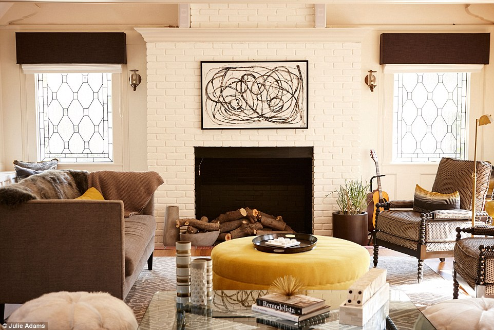 Unique: A living and entertainment area features brown retro style armchairs teamed with contemporary accents of abstract artwork and a round ottoman in a plush yellow velvet