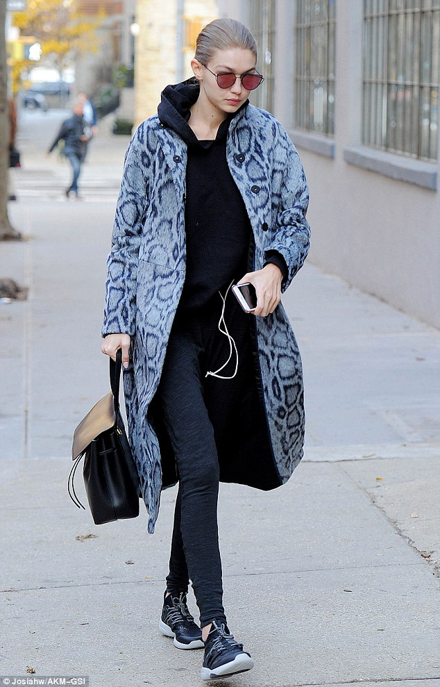 Casual cool: The 21-year-old model slithered in a long grey python patterned coat over a comfortable outfit while making it to her latest job
