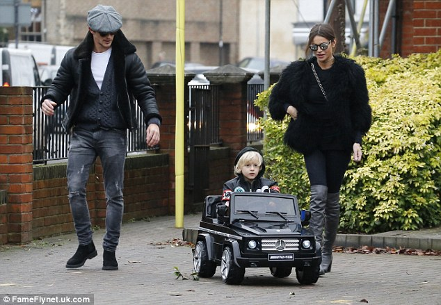 Cheaper than the real thing: Carrying the hefty toy, a £249 ride-on copy of the G Wagon, Jake looked to have stepped into his role as man of the house with ease