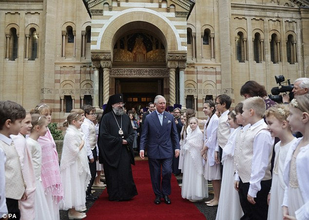 Archbishop Elisey walks with Prince Charles outside Dormition Cathedral after the service