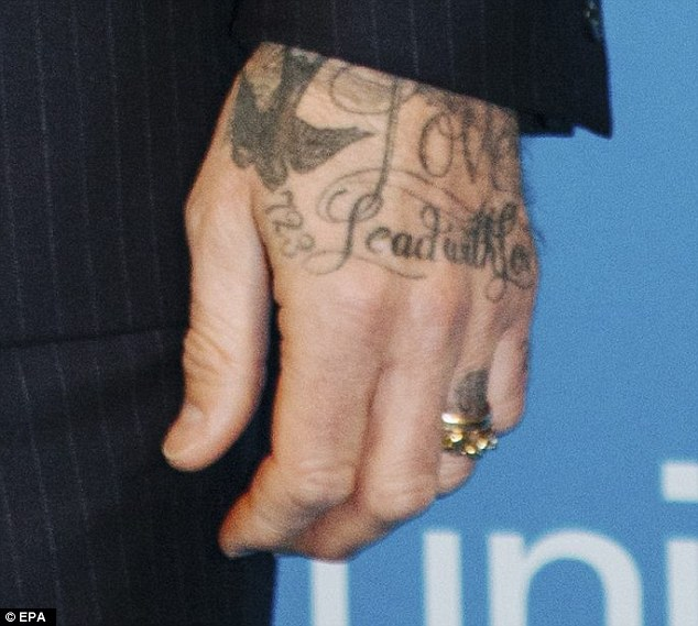 Something new: The UNICEF Goodwill Ambassador, 41, sported an unmistakably new ring, prompting speculation that wife Victoria Beckham has purchased the former footballer a new wedding band