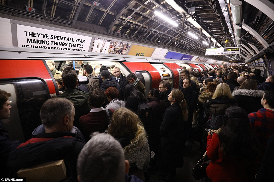 Passengers push on to an Underground train at Victoria station, which is usually a hub for Southern Rail services