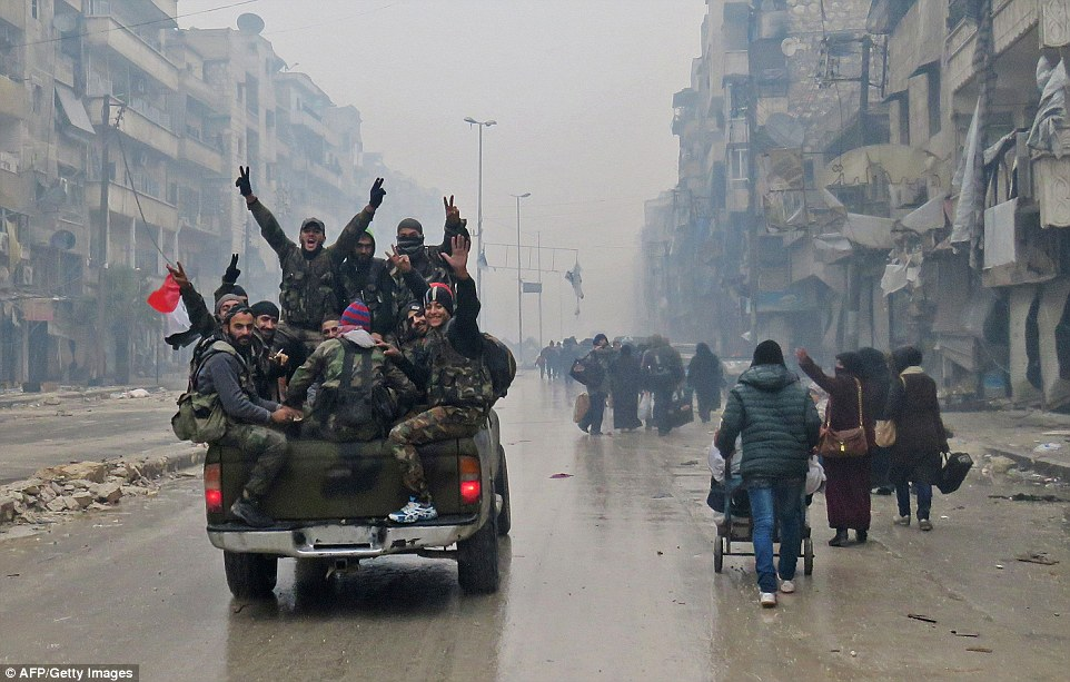 Syrian pro-regime fighters are pictured as they past resident fleeing residents in the Bustan al-Qasr neighbourhood of Aleppo today