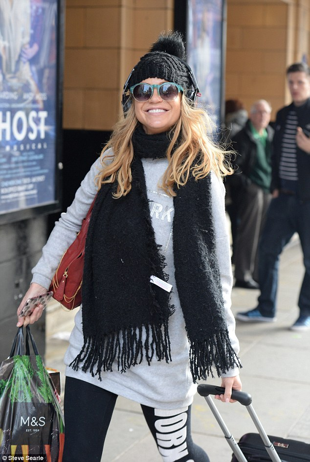 Happy: Grinning like a Cheshire cat, the former Girls Aloud singer layered on the comfy clothing as she navigated through the streets with her suitcase
