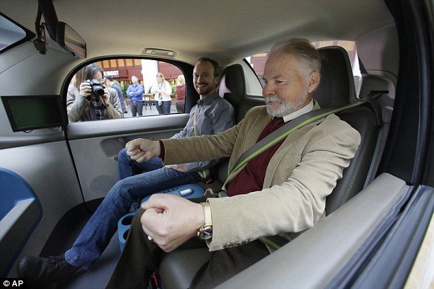 Steve Mahan, who is blind, gestures for a steering wheel that doesn't exist inside a Waymo driverless car during a Google event, Tuesday, Dec. 13, 2016, in San Francisco. At left is Waymo principal software engineer Nathaniel Fairfield. The self-driving car project that Google started seven years ago has grown into a company called Waymo.