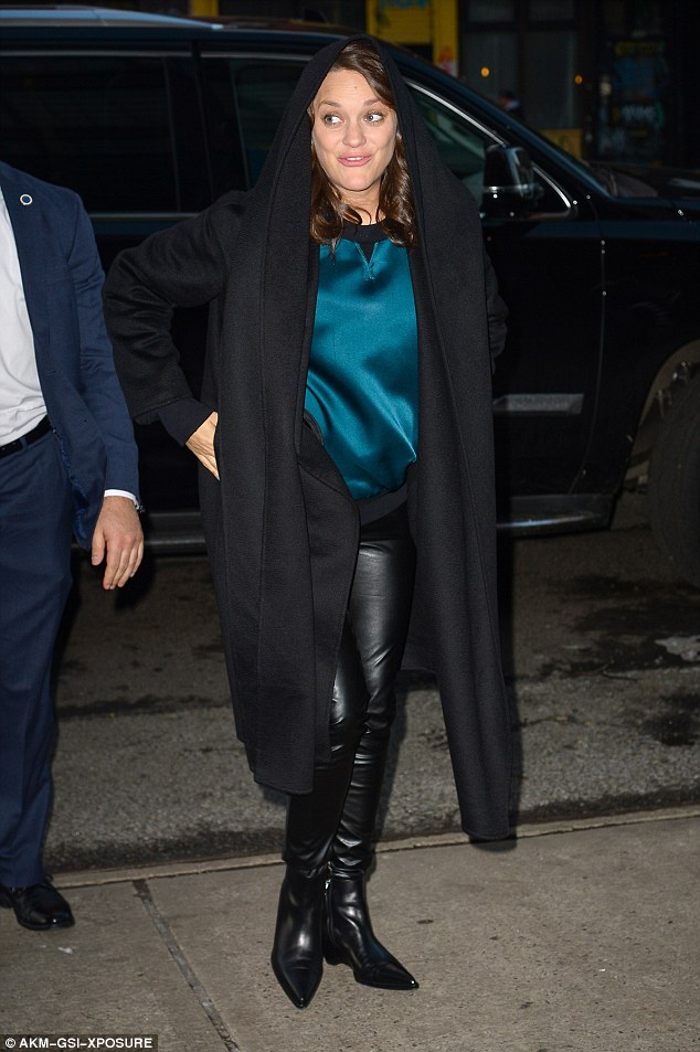 Happy! The pregnant actress covered her burgeoning bump with a baggy blue satin sweater and a billowing black overcoat