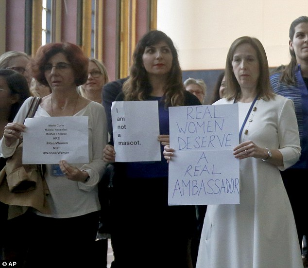 Real deal: Two protesters at the UN hold up signs complaining that real women should have been given the role, while another appears to object to real women being used as mascots