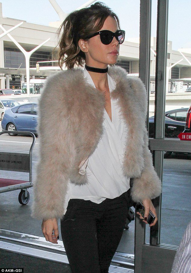 Rockstar look: The 43-year-old actress - who was nominated for Best Actress in a Comedy for her role in Love & Friendship - wore a deep neckline white blouse underneath a stylish cotton candy fur jacket as she headed through LAX
