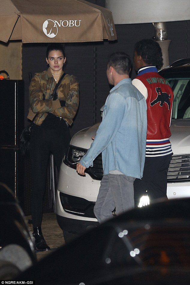Impatiently waiting: With her hair scraped up into a bun and accessorising with delicate necklaces, she stood alongside A$AP as they waited for her Ferrari to be brought around