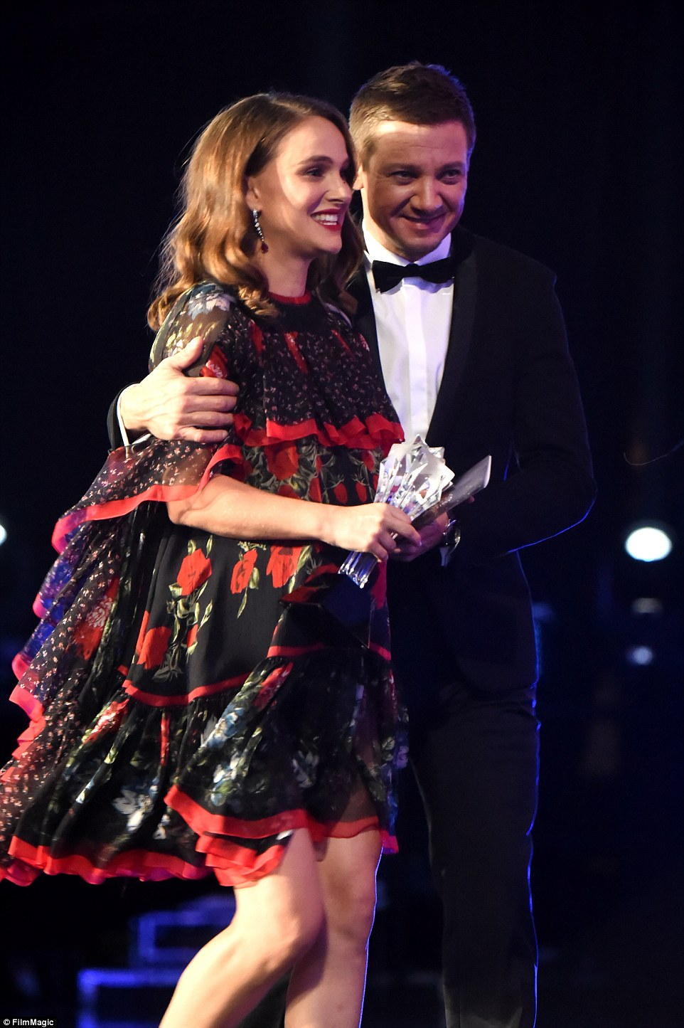 Helping hand: Jeremy Renner put his arm around Natalie as they walked off stage together