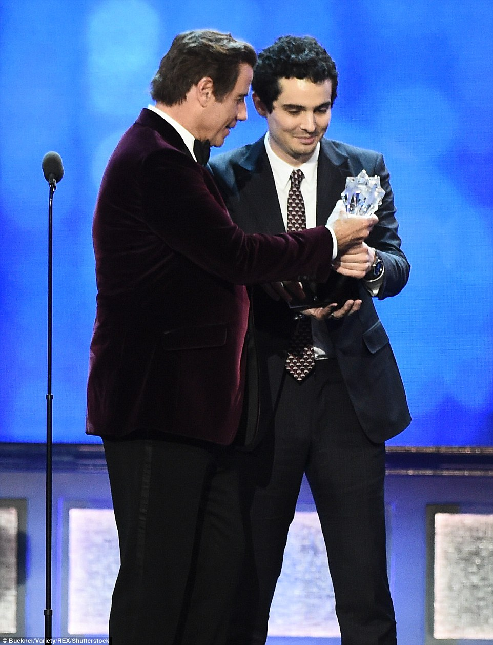 Eyes on the prize: Director Damien Chazelle was presented with the Best Picture award for La La Land by John Travolta